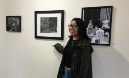 Elizabeth Perez posing with her work at RCCC's Autumn Exhibition