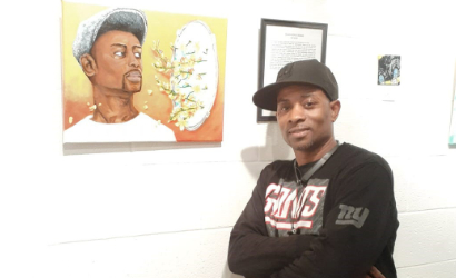 Poet, Jah Small, posing next to his portrait in the Black Kings Exhibition