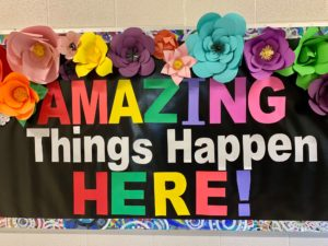 """Bulletin board decorated with text that reads, """"Amazing things happen here!"""""""