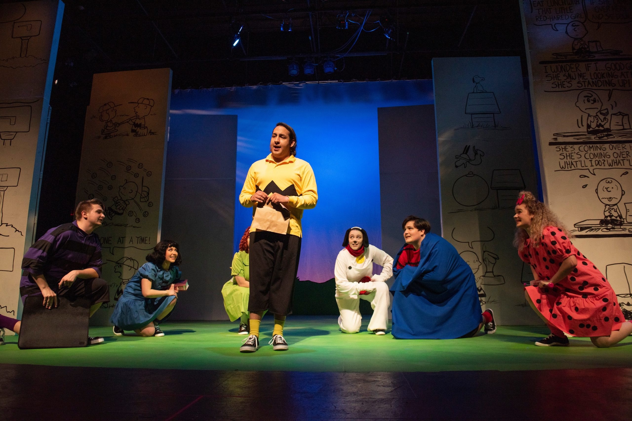 actor playing the Charlie Brown character on stage with other actors looking on