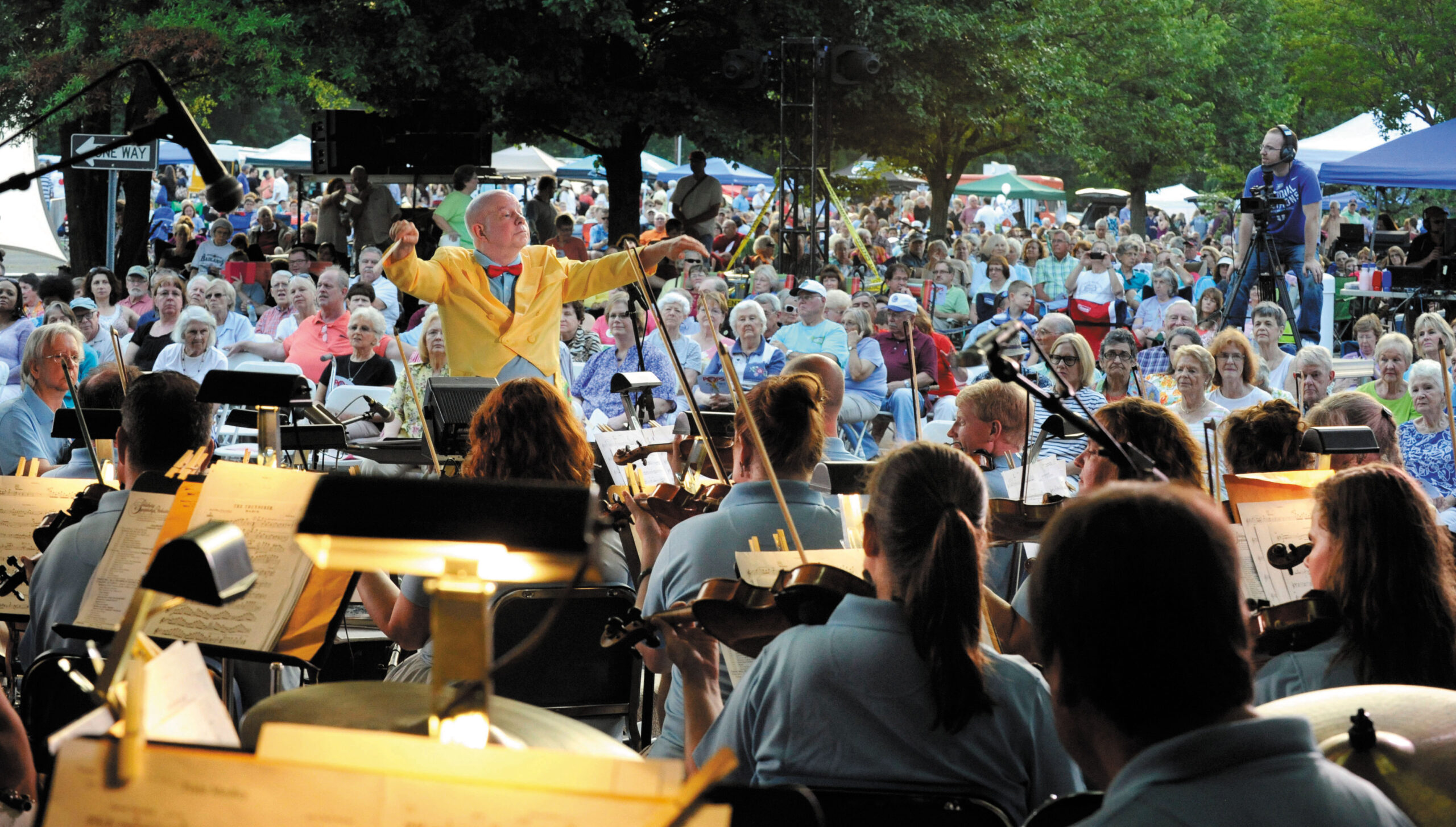 Conductor David Hagy leads the music at the Salisbury Symphony's Pops at the Post with a crowd behind them watching.